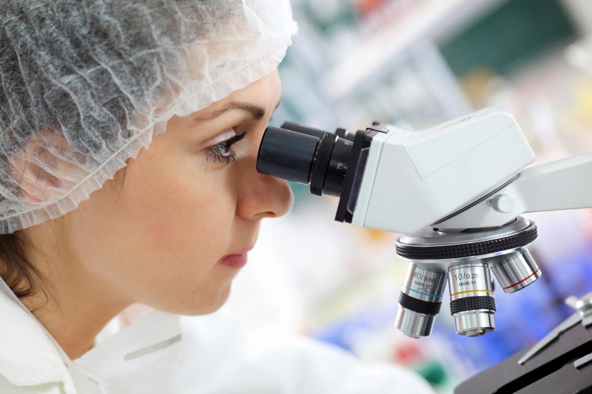 Kvinne ser inn i mikroskop. Foto.