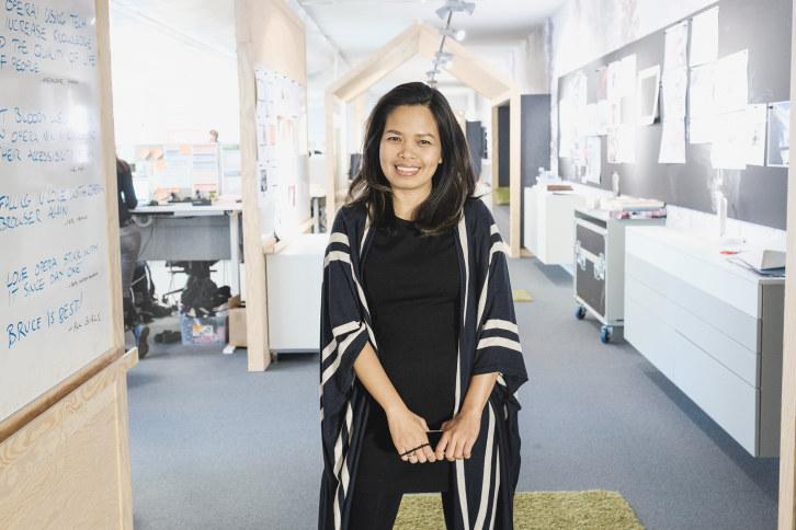 Kvinne med asiatisk utseende står i en kontorgang hos Opera og ser i kamera.