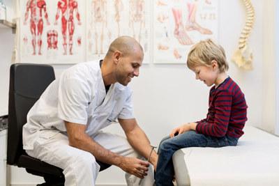 Mannlig doktor sjekker knereflekser hos en gutt på ortopedisk klinikk