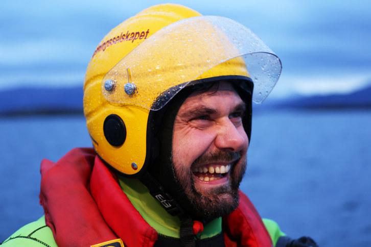 Mann med skjegg og hjelm ler