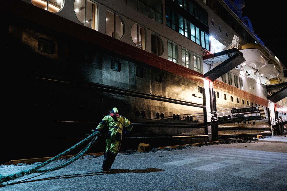 Person jobber på havna på natten. Foto.