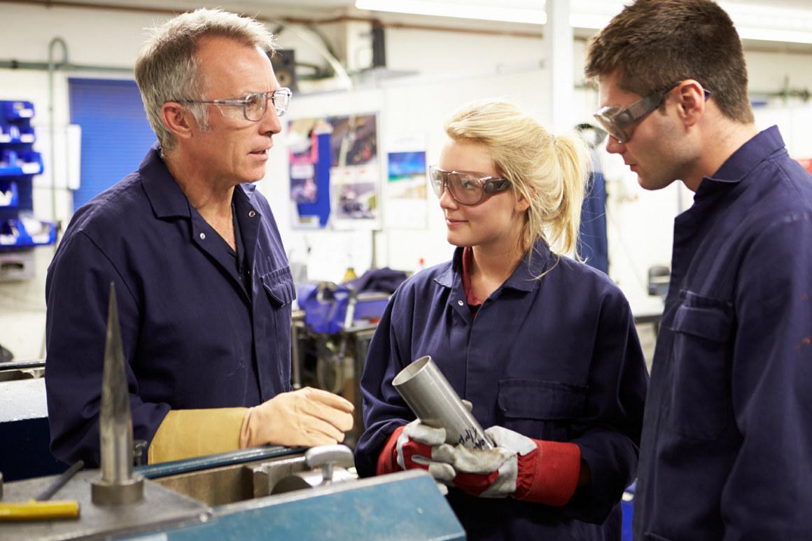 Lærer og to elever i et verksted. Foto.