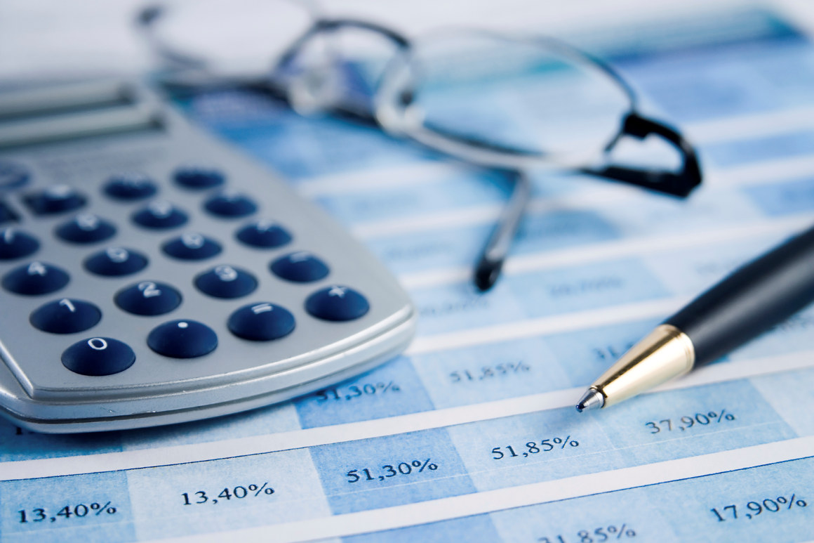 Kalkulator, briller og penn liggende på en papirtabell. Foto.