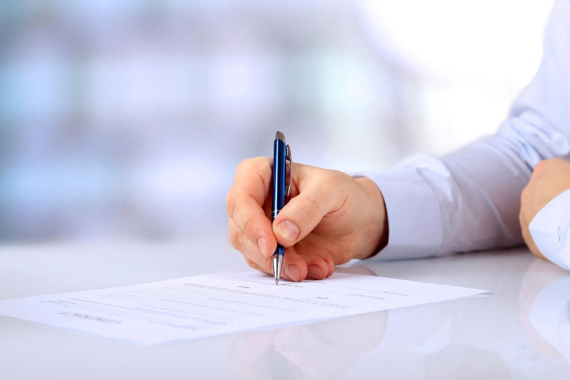 Person underskriver dokument. Foto.