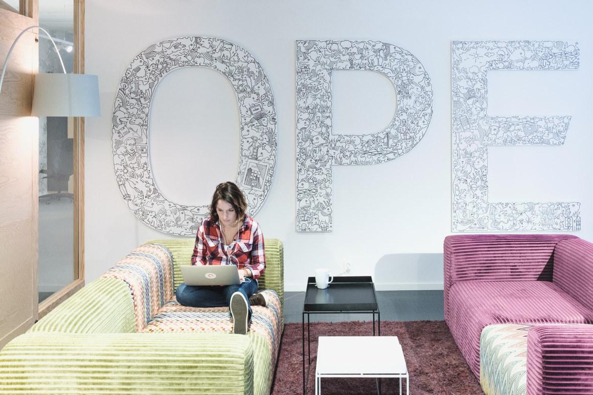 Kvinne jobber på Mac i en sofa hos bedriften Opera. Foto.