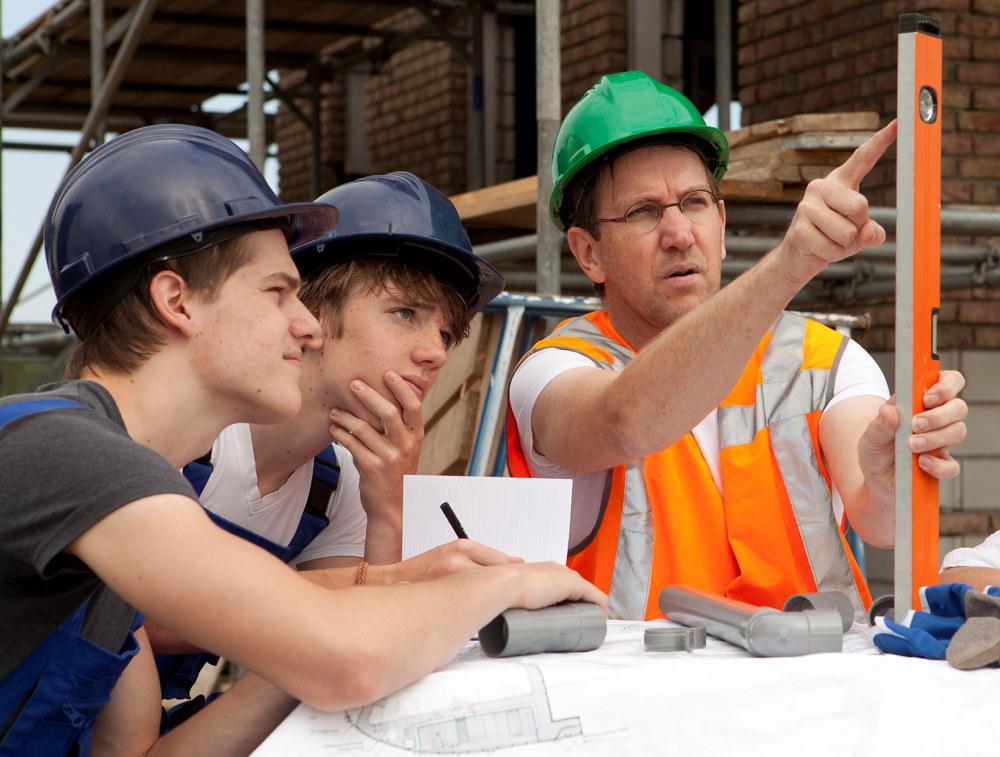 To lærlinger og sjefen deres på en byggeplass.