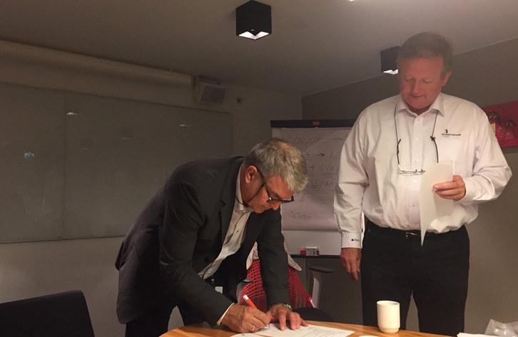 HR-direktør Reidar Kleven signerer avtalen i møte med prosjektleder Paal Haavorsen i NHO Service (Foto: Ragnhild Friis-Ottesen)
