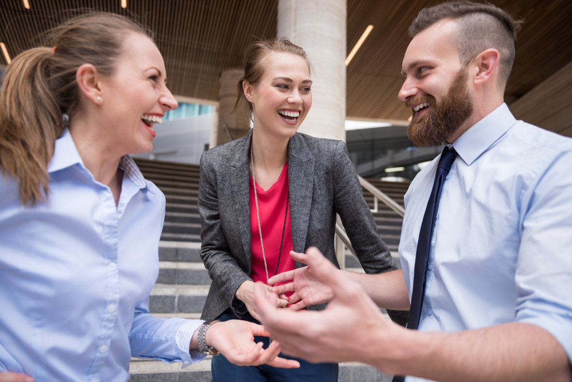 Tre personer smiler og ler. Foto.