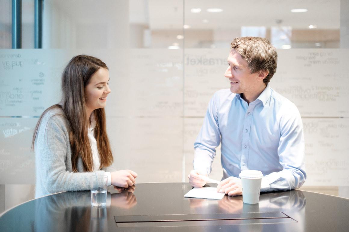 Mann og kvinne snakker sammen i et møte. Foto.