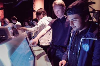 Elever løser oppgaver foran skjerm i NHO Besøkssenter.