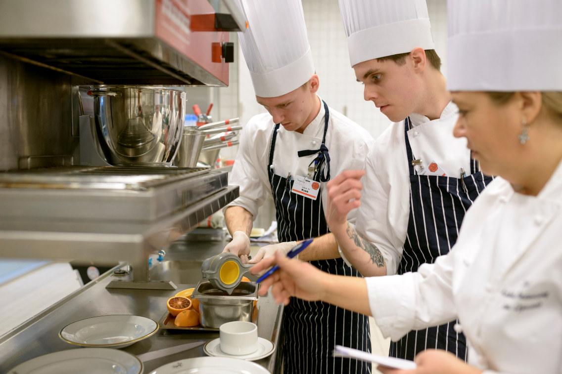 Tre kokker på et kjøkken. Foto.