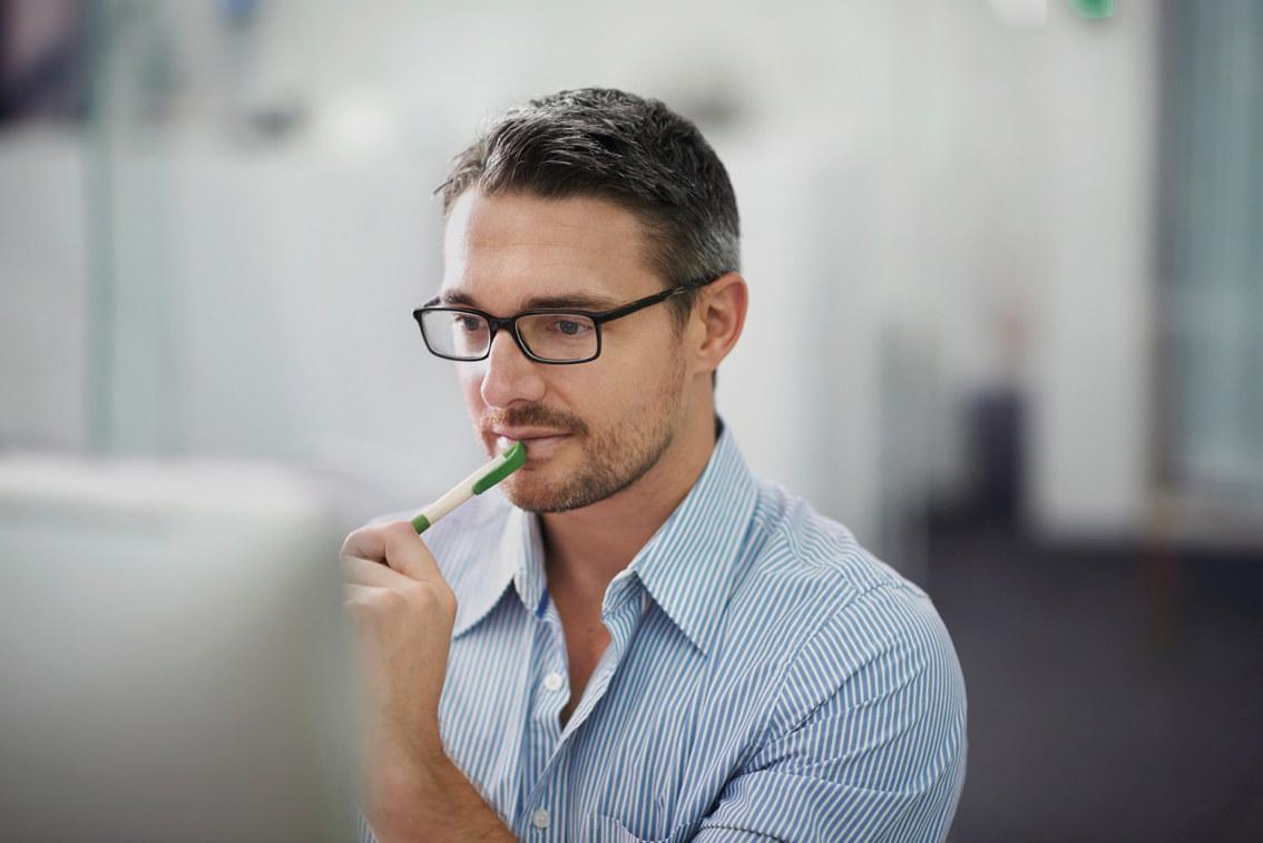 Tenkende mann på kontor. Foto.