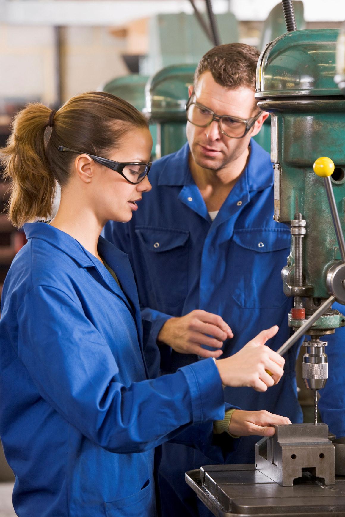 Mann og kvinne jobber på verksted. Foto.