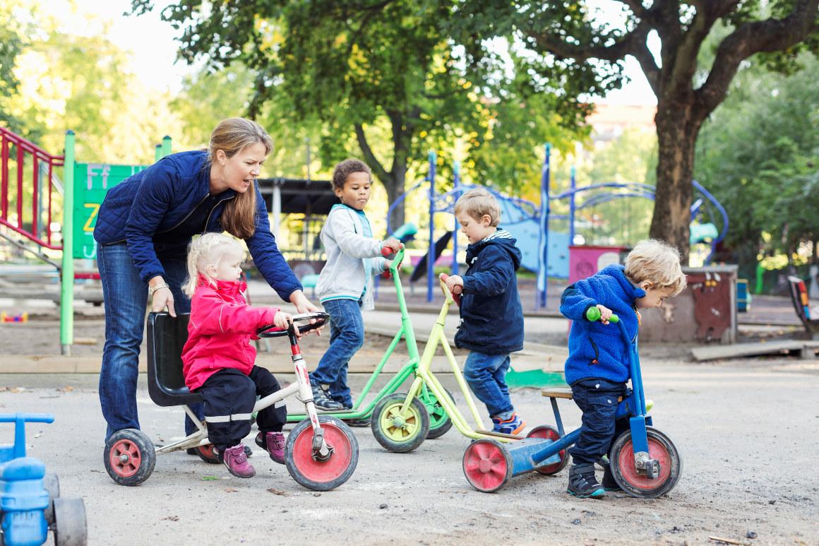 Barn og ansatt i lek i barnehage. Foto.