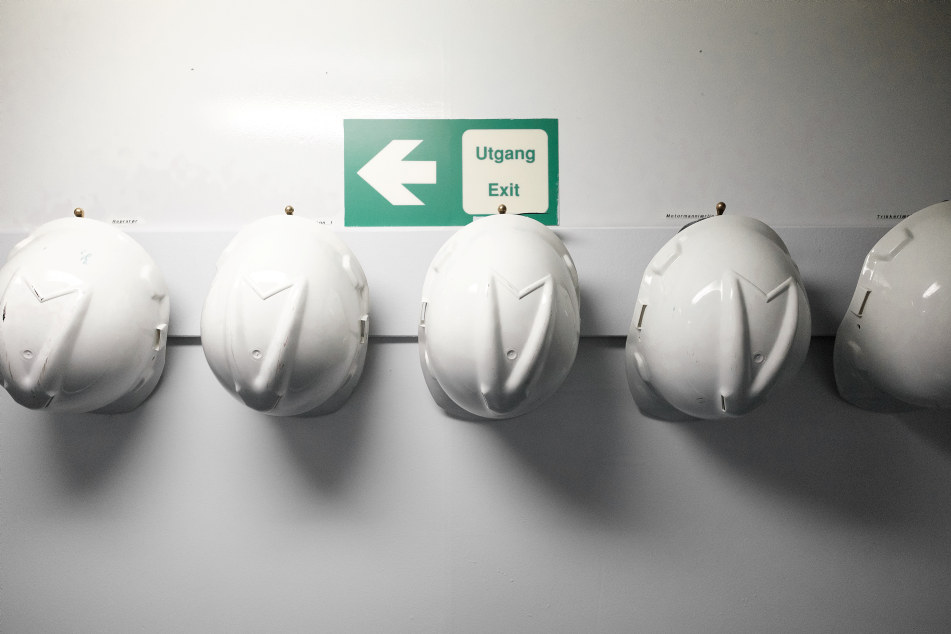 Hvite hjelmer på vegg nødutgangskilt