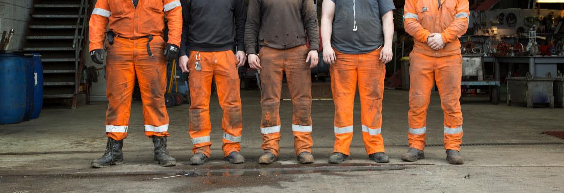 Fem personer i arbeidstøy står på rekke og rad. Foto.
