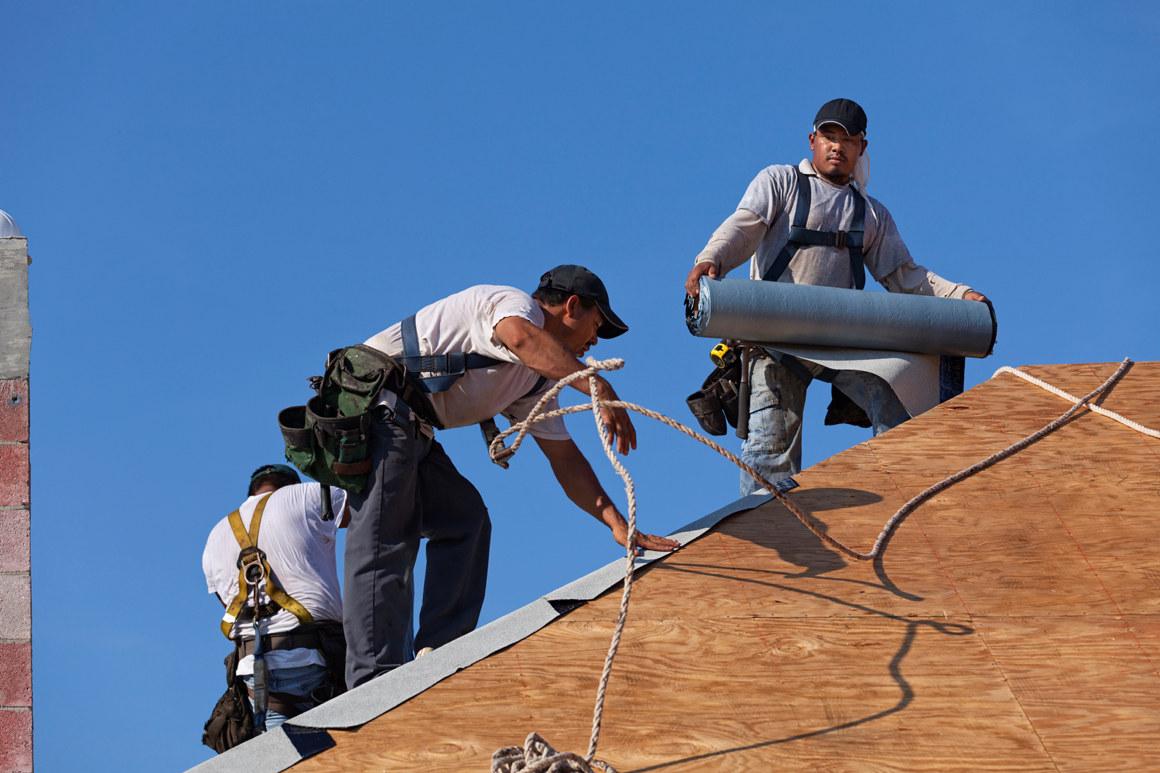 Arbeidere jobber på et tak. En mann holder et tungt rør med takbelegg. Foto.