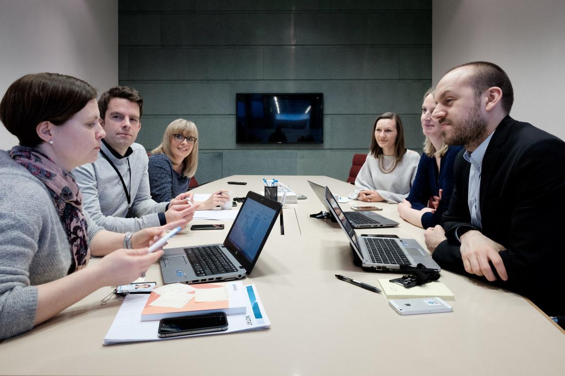 Mennesker rundt møtebord. Foto.