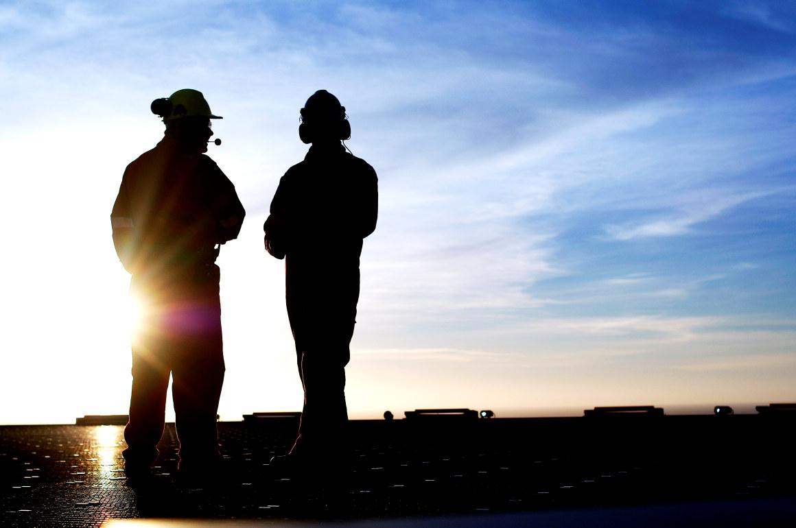 Silhuett av to personer i arbeidstøy. Foto.