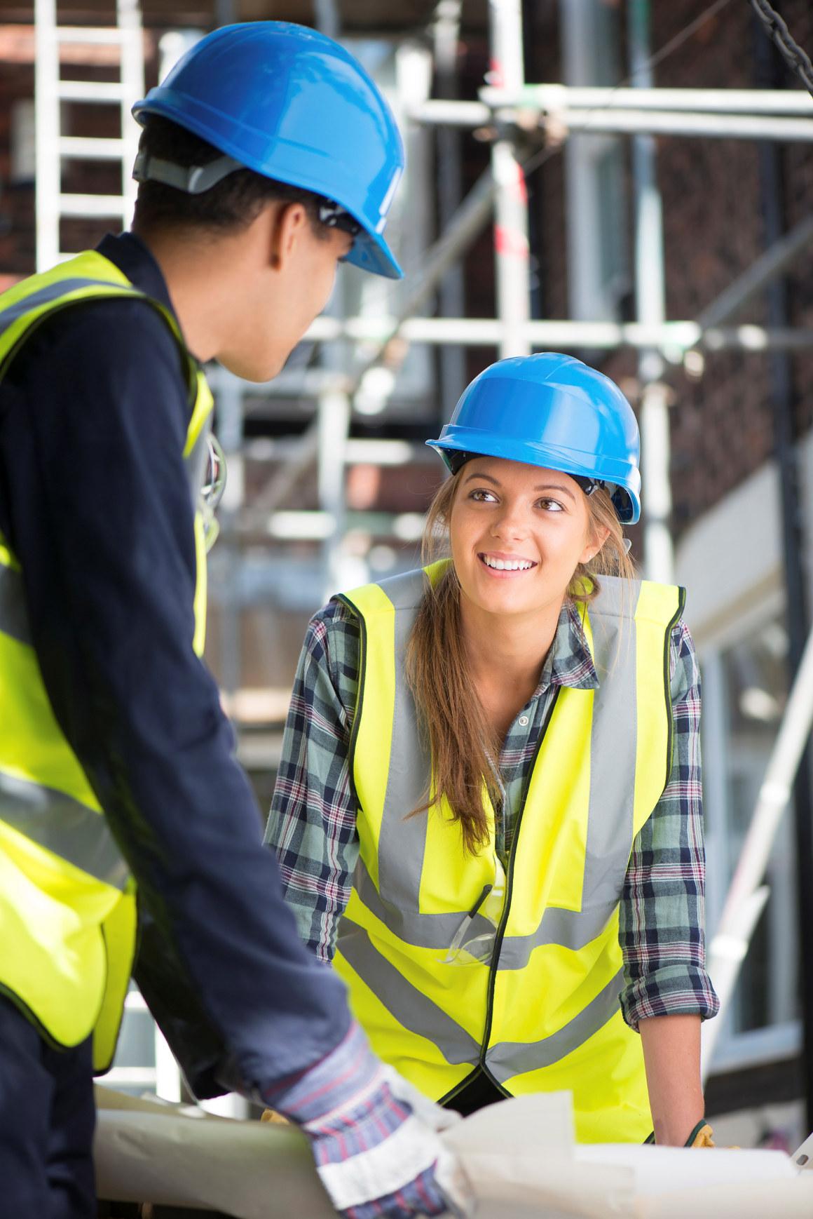 Mann og kvinne i verneutstyr på byggeplass. Foto.