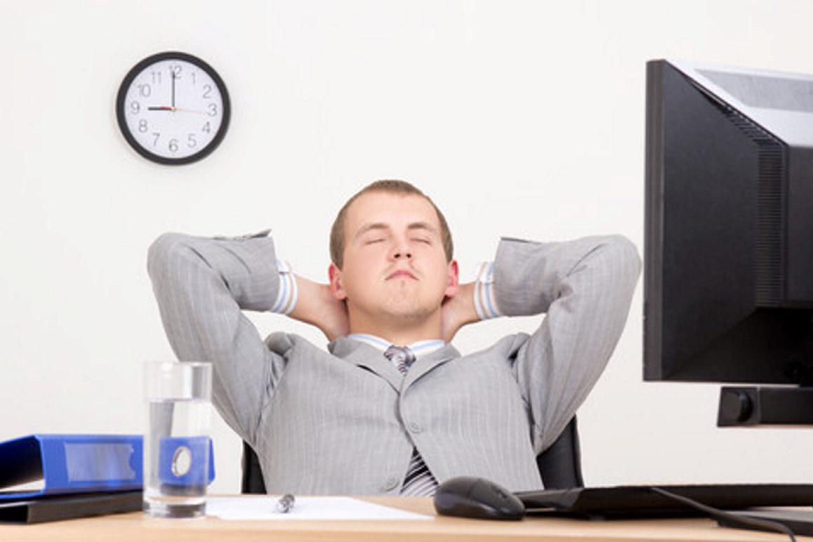 Sliten mann i kontorstol, med lukkede øyne. Foto.