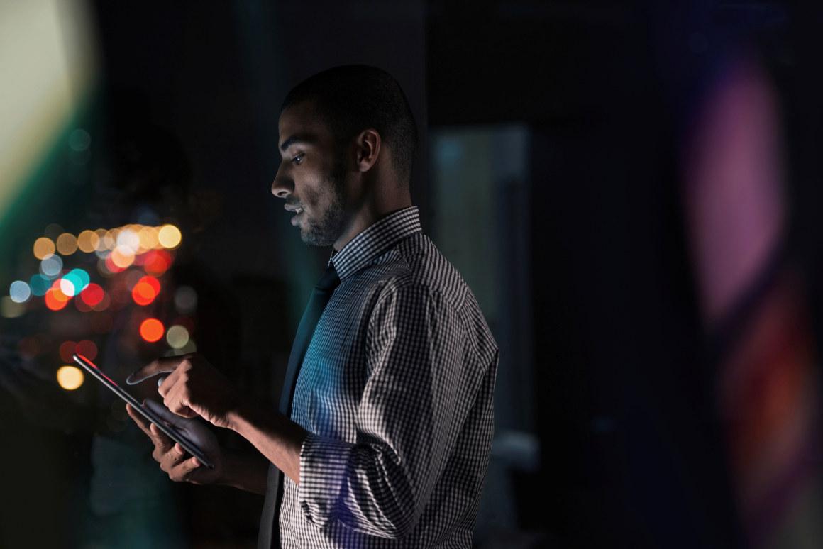 Mann arbeider alene på nettbrett på kvelden. Foto.