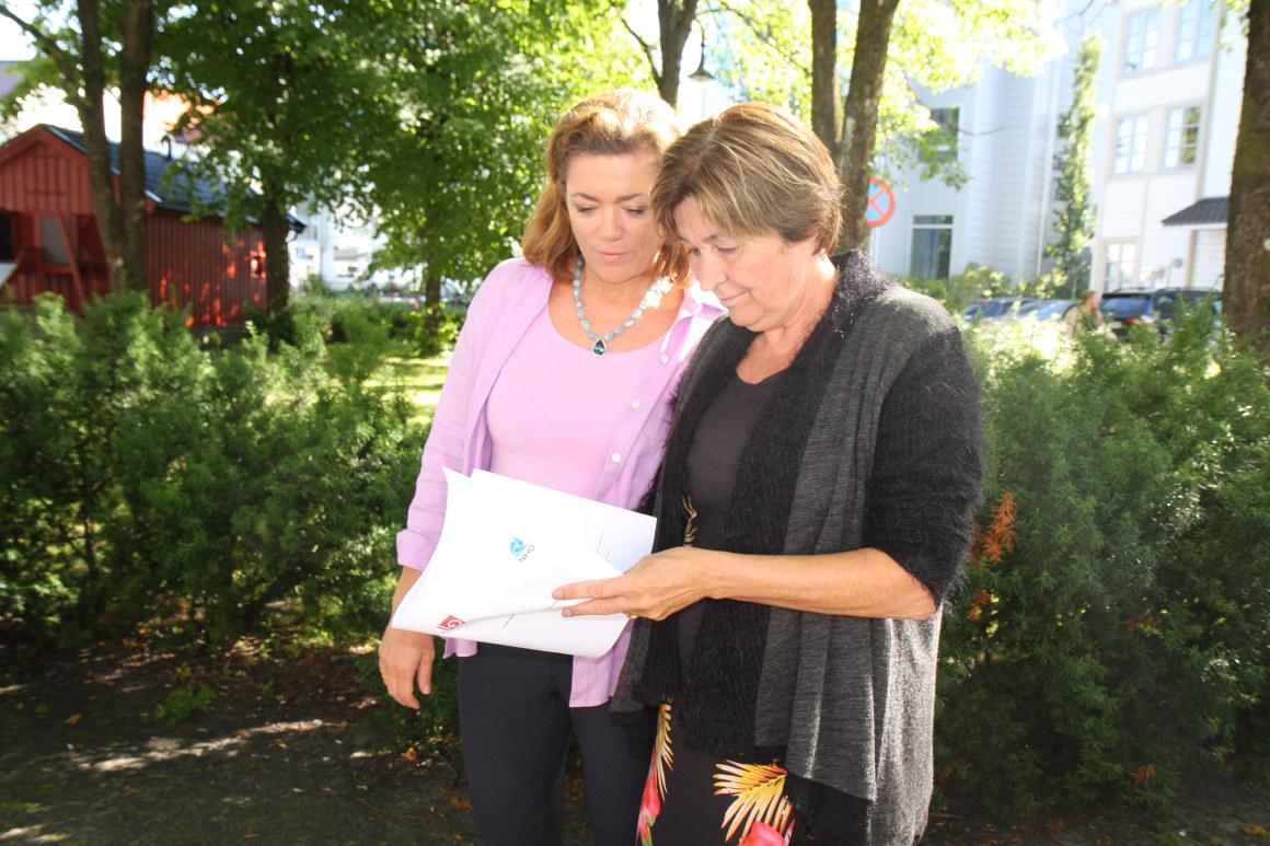 Kristin Skogen Lund og Gerd Kristiansen ser på et dokument. De står utendørs. Foto.
