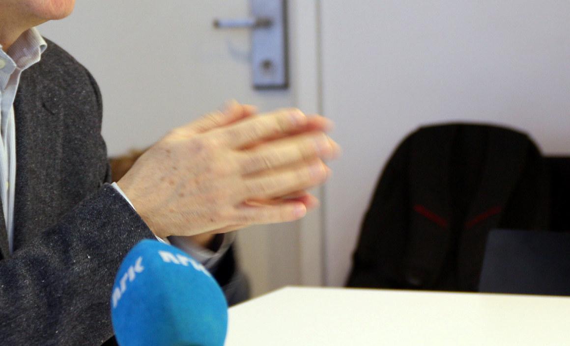 NRK-mikrofon, radiointervju, mann snakker. Gestikulerende hender. Foto.