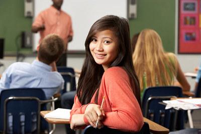 En jente i et klasserom snur seg og ser i kamera.