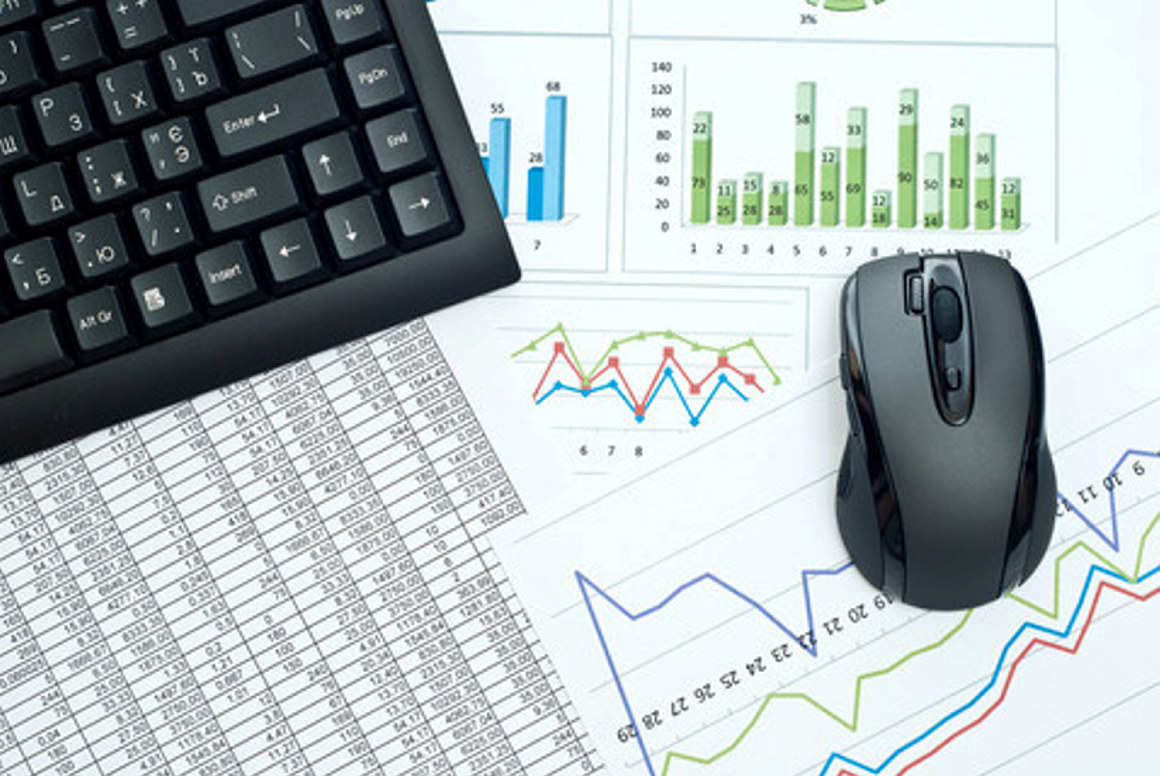 Tastatur og mus liggende på grafer, tabeller og andre dokumenter. Foto.