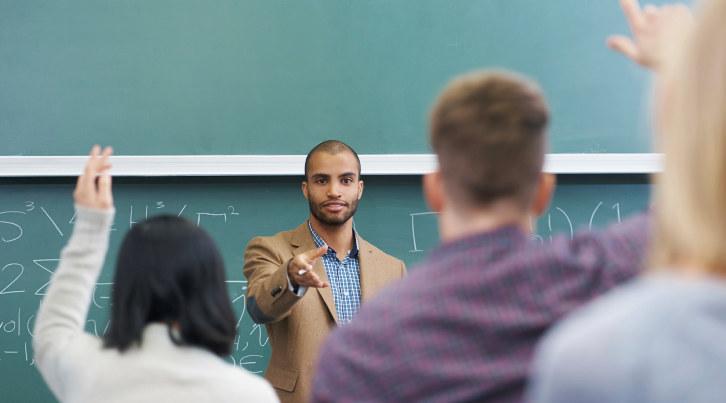 Lærer underviser. Elever har hånd i været.