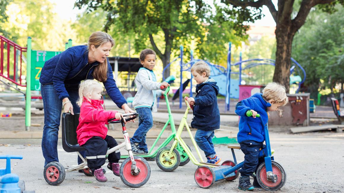 Kvinne og flere barn. Barna leker.