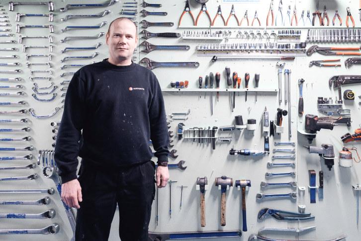 Maskinist på Hurtigruten foran en vegg med verktøy.