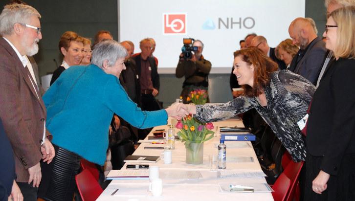LOs leder Gerd Kristiansen og NHOs administrerende direktør Kristin Skogen Lund rekker hverandre hånden.
