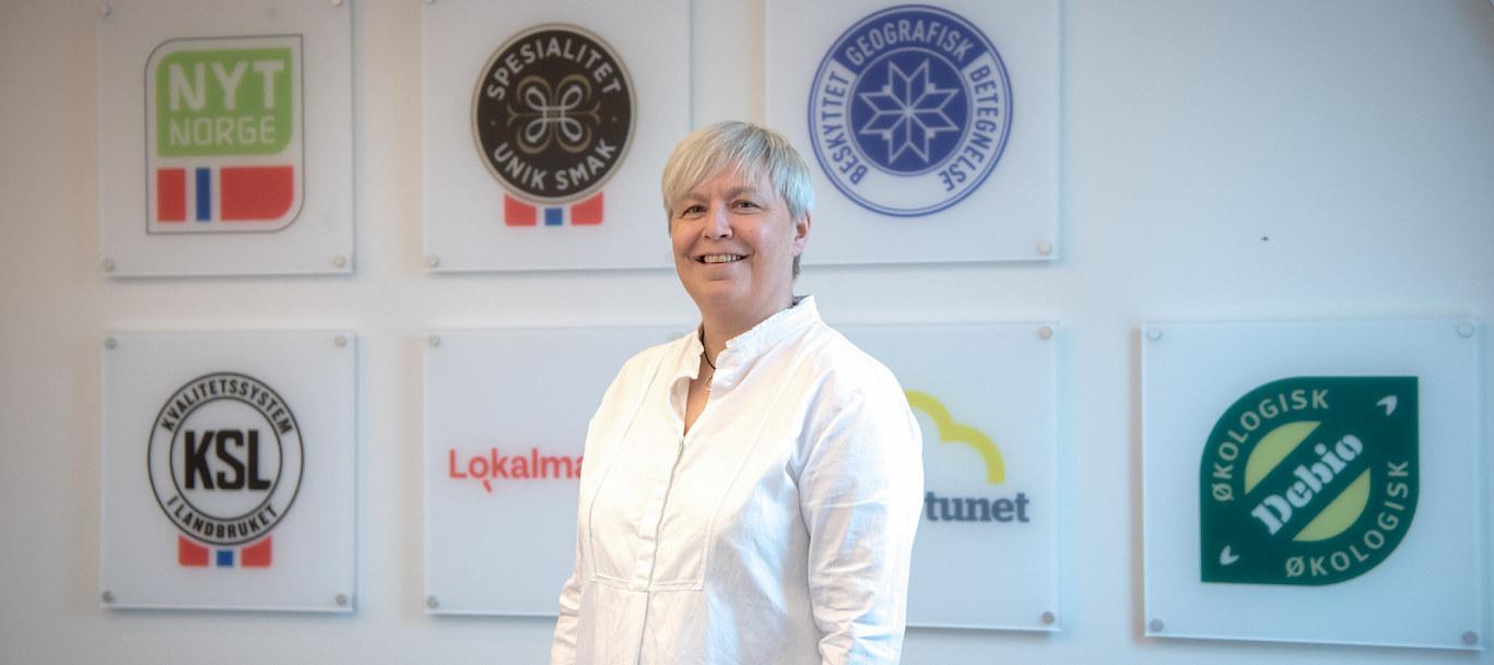Administrasjonssjef Mette Sørensen i Matmerk foran en vegg med merker de jobber med.