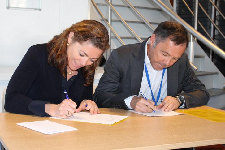 NHO-sjef Kristin Skogen Lund og departementsråd Tom Rådahl signerer NOx-avtalen