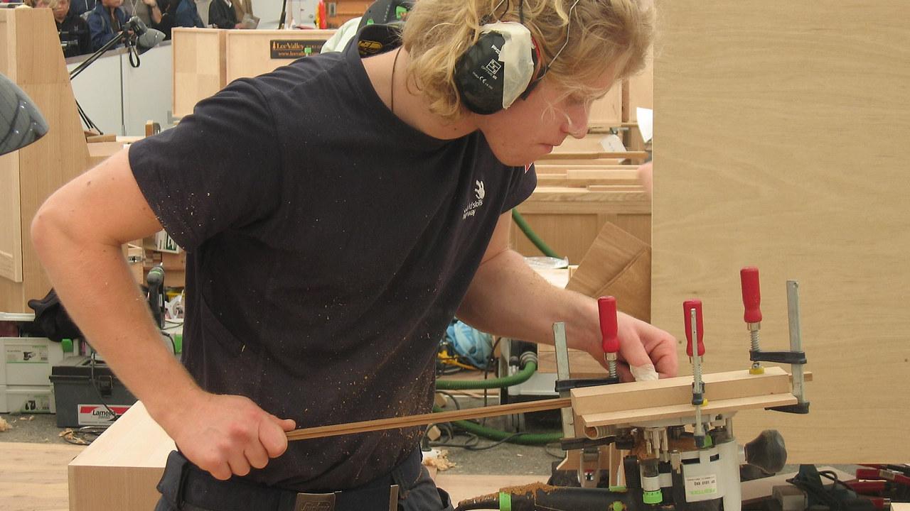 En tømrerstudent med hørselvern som sager til en list.