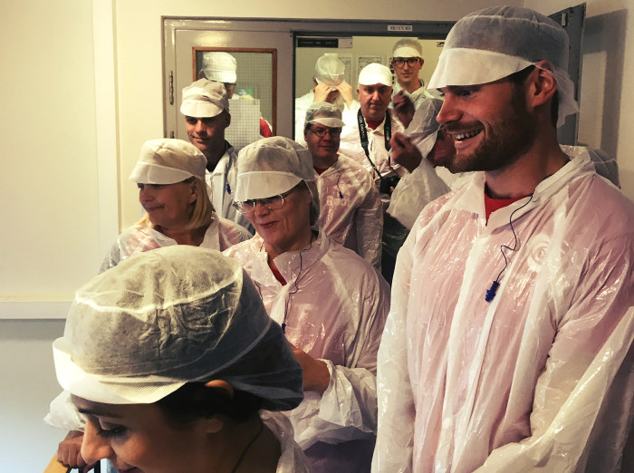 Mennesker ikledd hvite drakter som skal hindre smittespredning i fabrikken