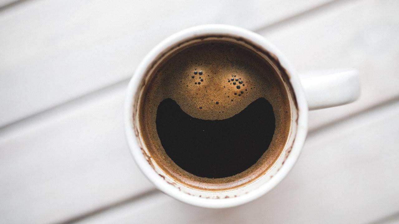 En kaffekopp der skummet er formet slik at det ser ut som et smilefjes.