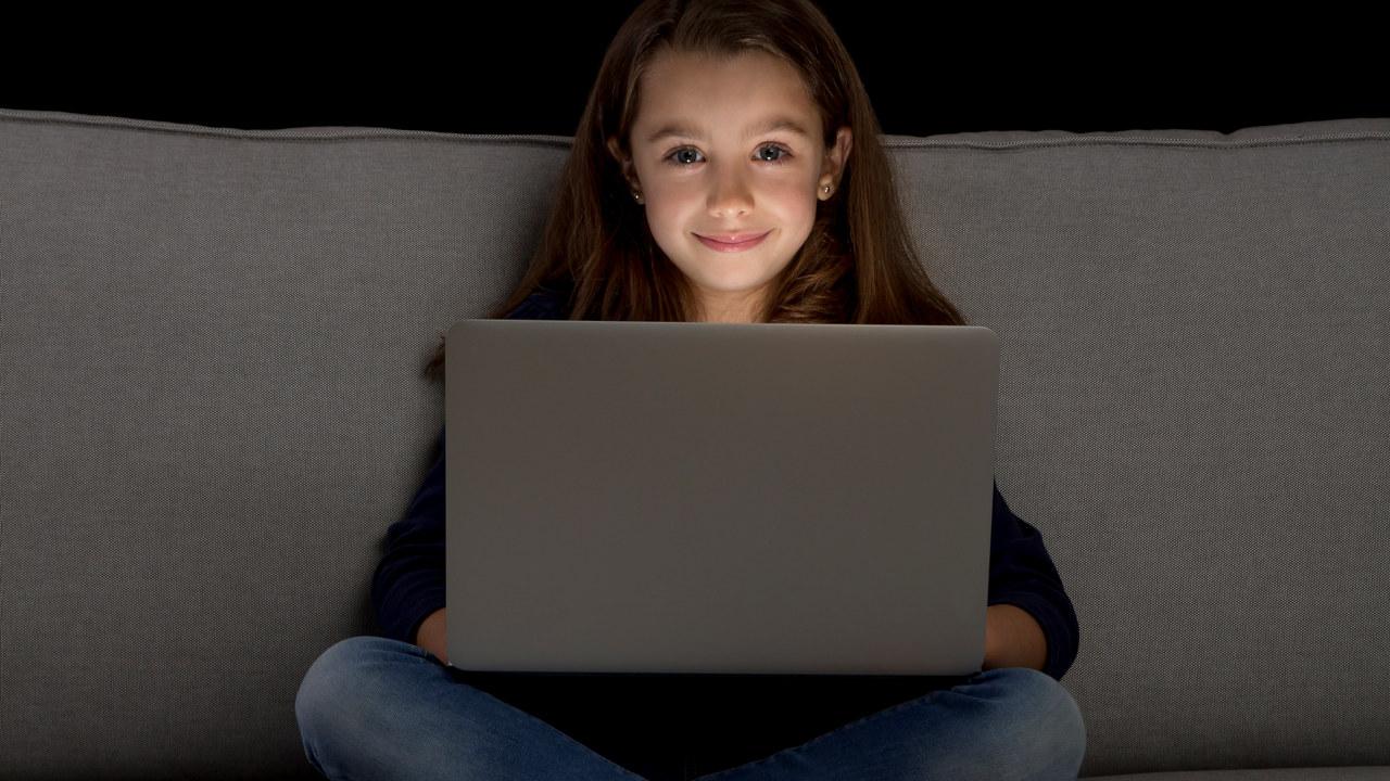Jente i sofaen med datamaskin - illustrasjonsfoto.