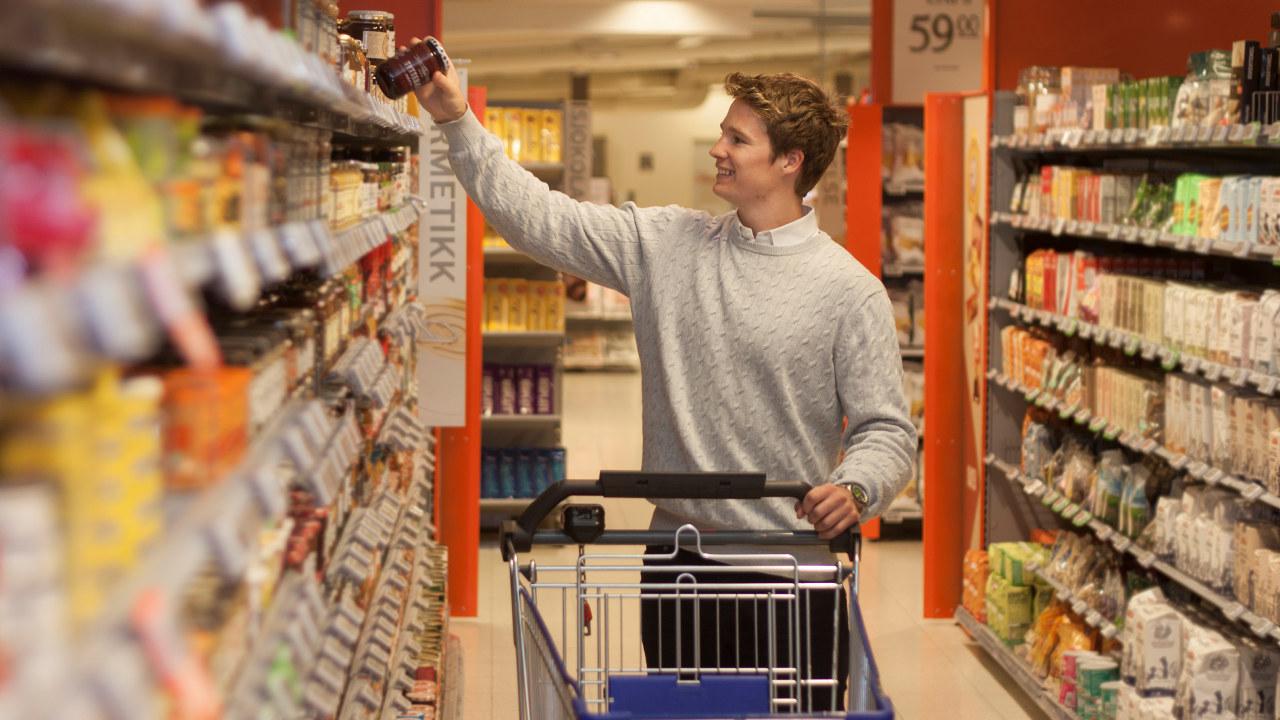 Ung gutt med handlevogn i butikk som henter ned en vare fra en butikkhylle