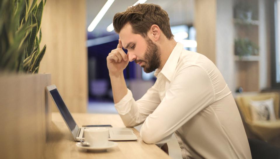Mann sitter ved en PC, tenker og støtter hodet med hånden.