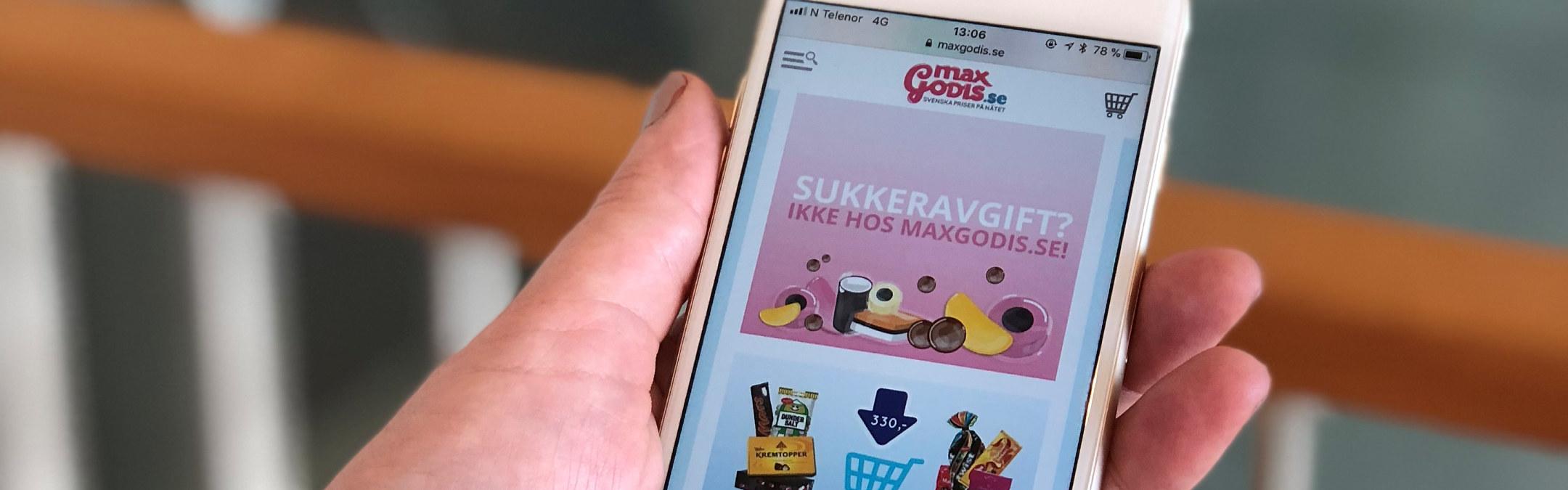 Nærbilde av en mobiltelefon som har nettsiden til MaxiGodis åpen i nettleseren