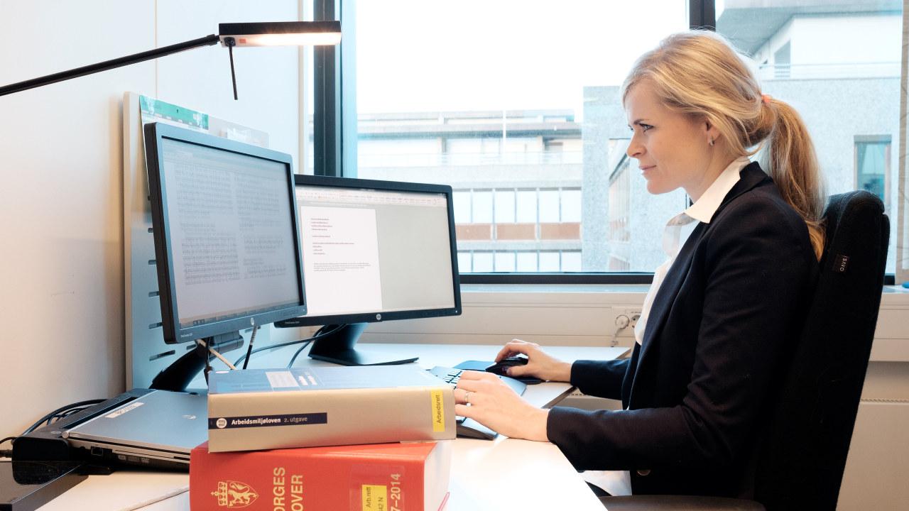 En dame som sitter å skriver på en PC.