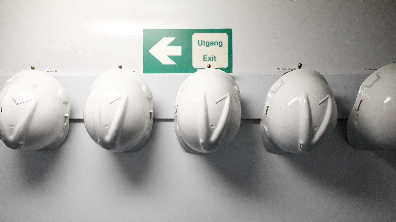 Arbeidshjelmer hengt opp på en vegg.