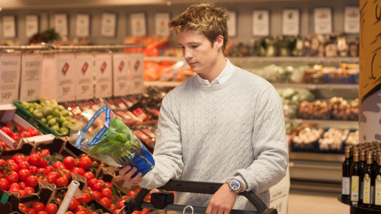 En ung mann som handler i en butikk. Han holder en basilikum i hånden.