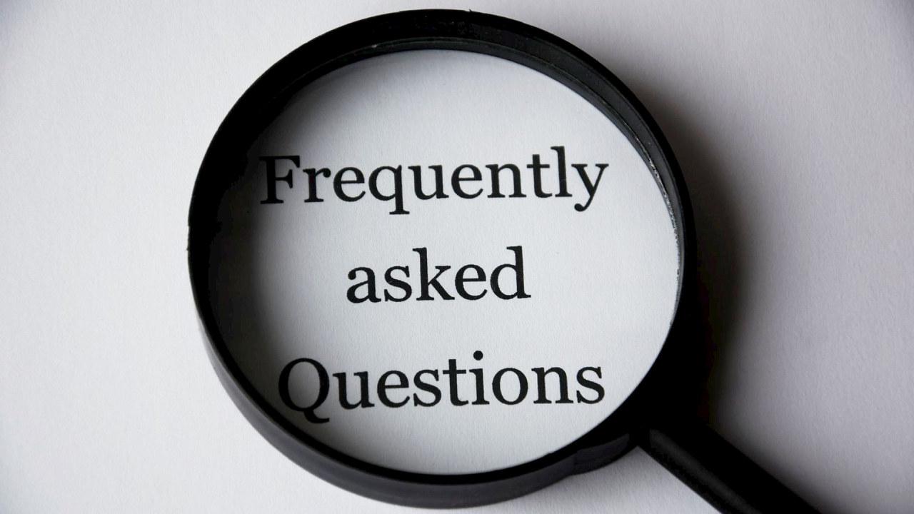 Et forstørrelsesglass som ligger på et papir der det står skrevet: Questions and answers