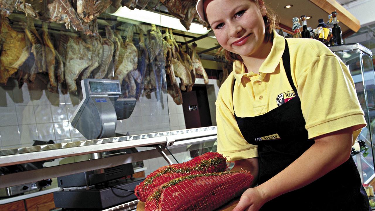 En butikkslakter viser frem et kjøttstykke fra ferskvaredisken i en butikk