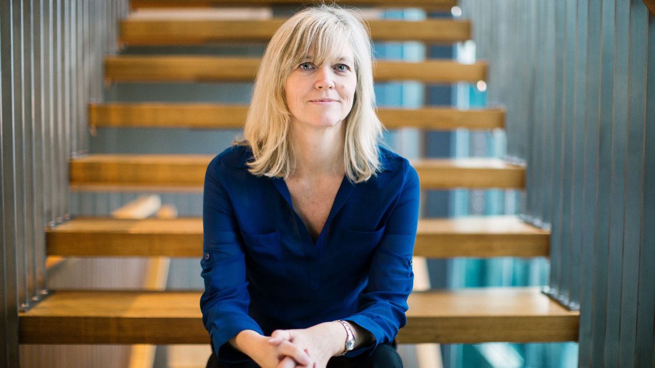 Nina Melsom, direktør for arbeidsliv i NHO, sitter på en trapp i Næringslivets Hus på Majorstua.