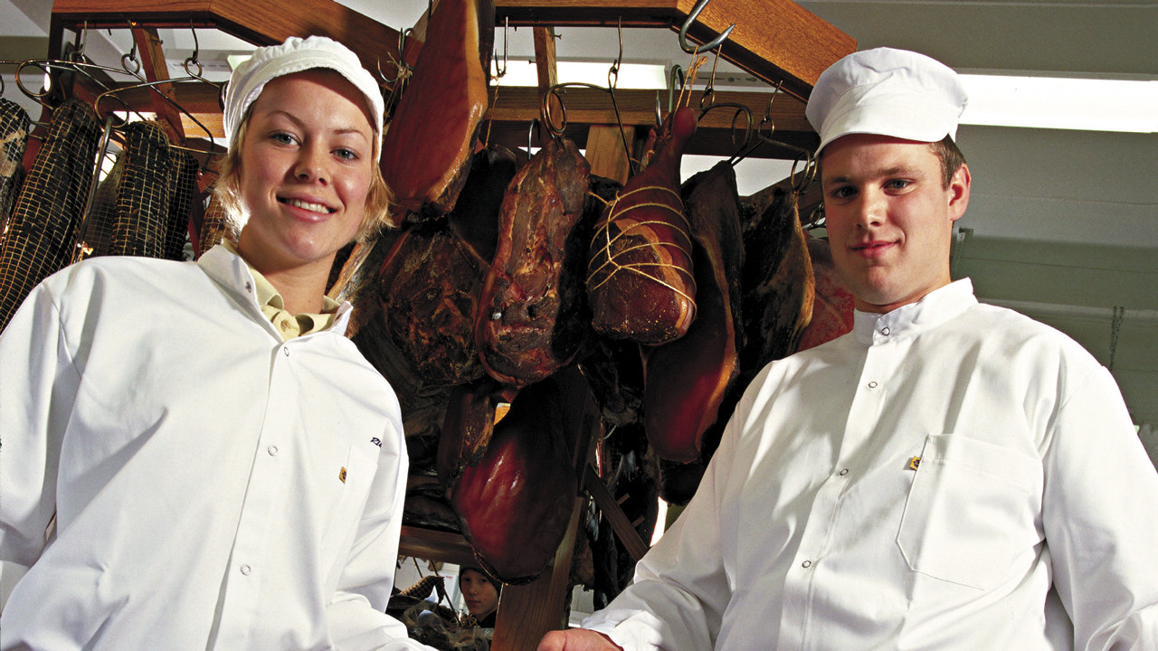 To pølsemakere som står foran en stabel med pølser
